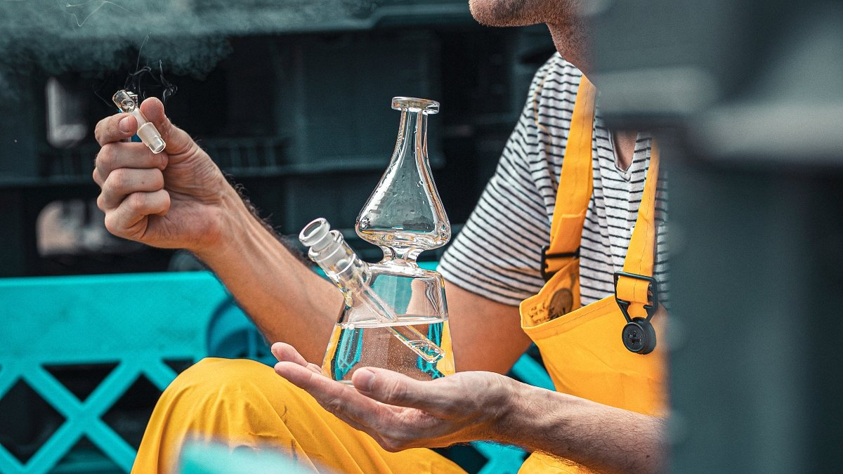 Person smoking cannabis from a glass bong