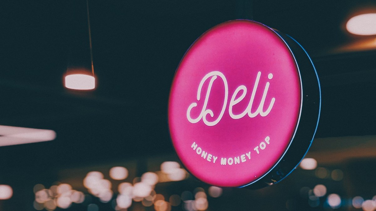 Deli logo sign on a pink neon light in a dark background