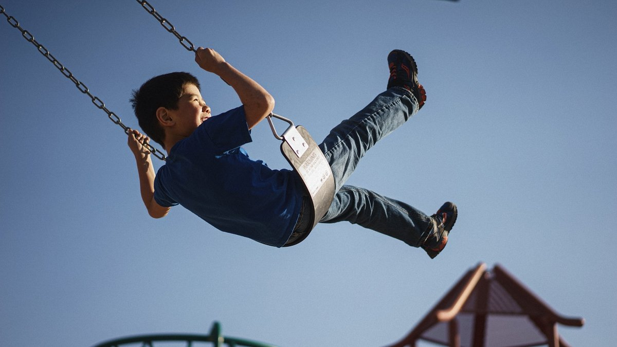 A child having a fun time with a swing in a blue sky background