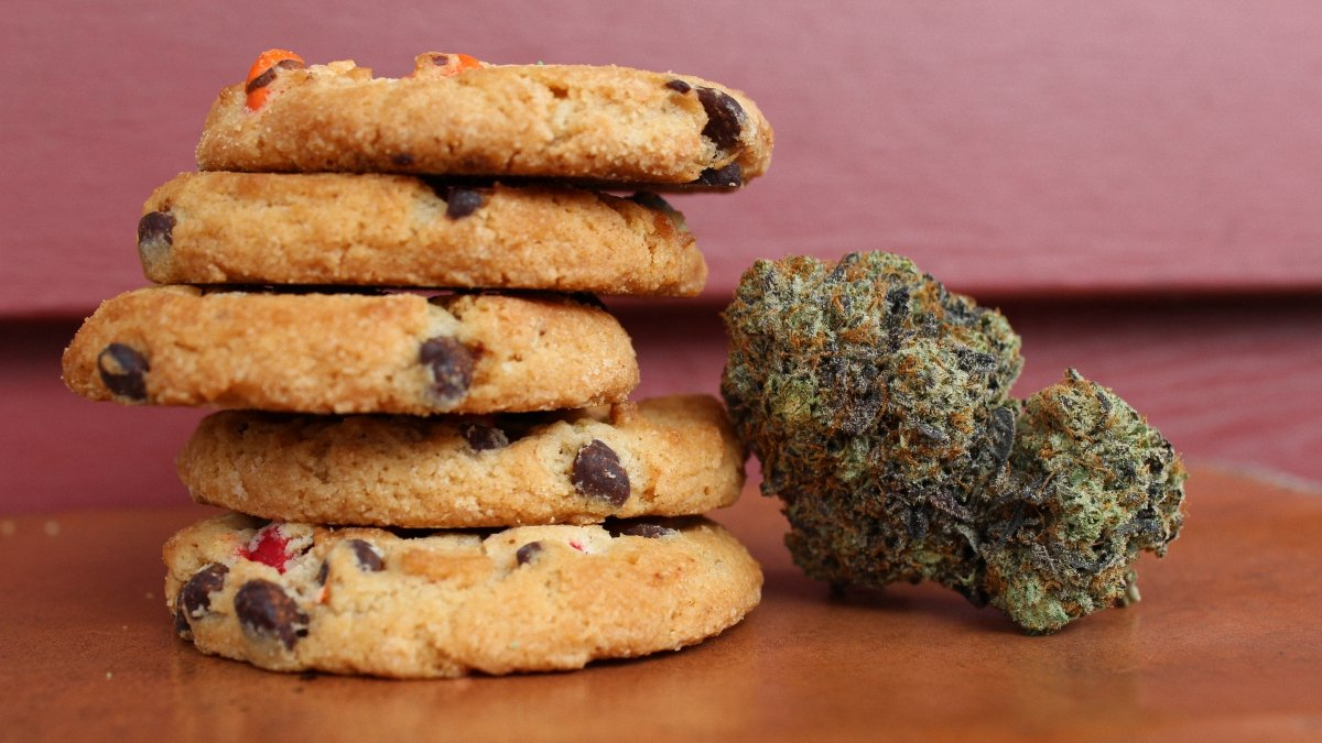 A pile of baked cookies next to a cannabis bud