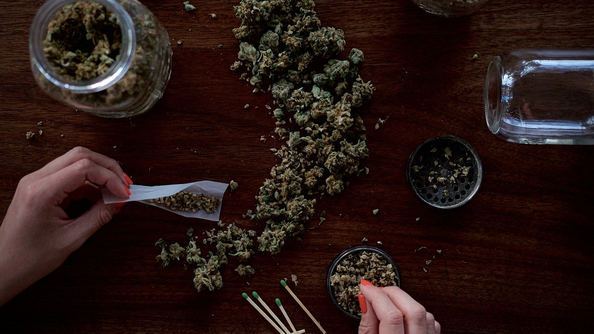 Person rolling a marijuana paper joint on a wooden table with cannabis lying around