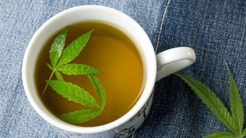 Marijuana tea inside a teacup with cannabis leaves floating inside