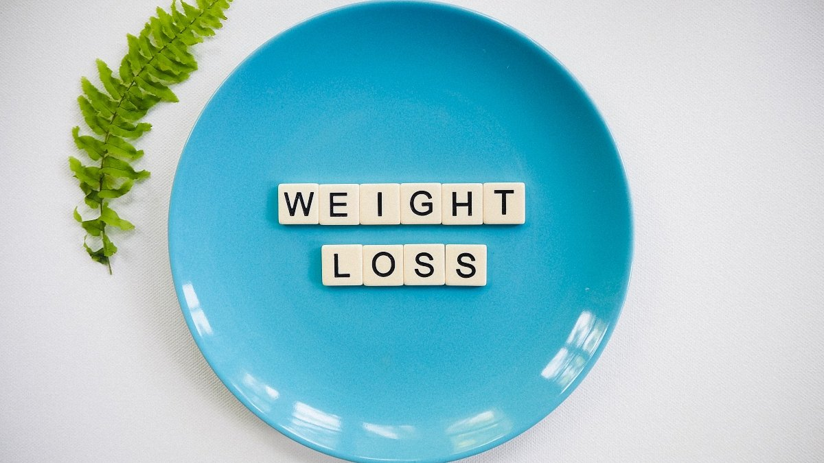 A blue plate with alphabetical cubes that read weight loss