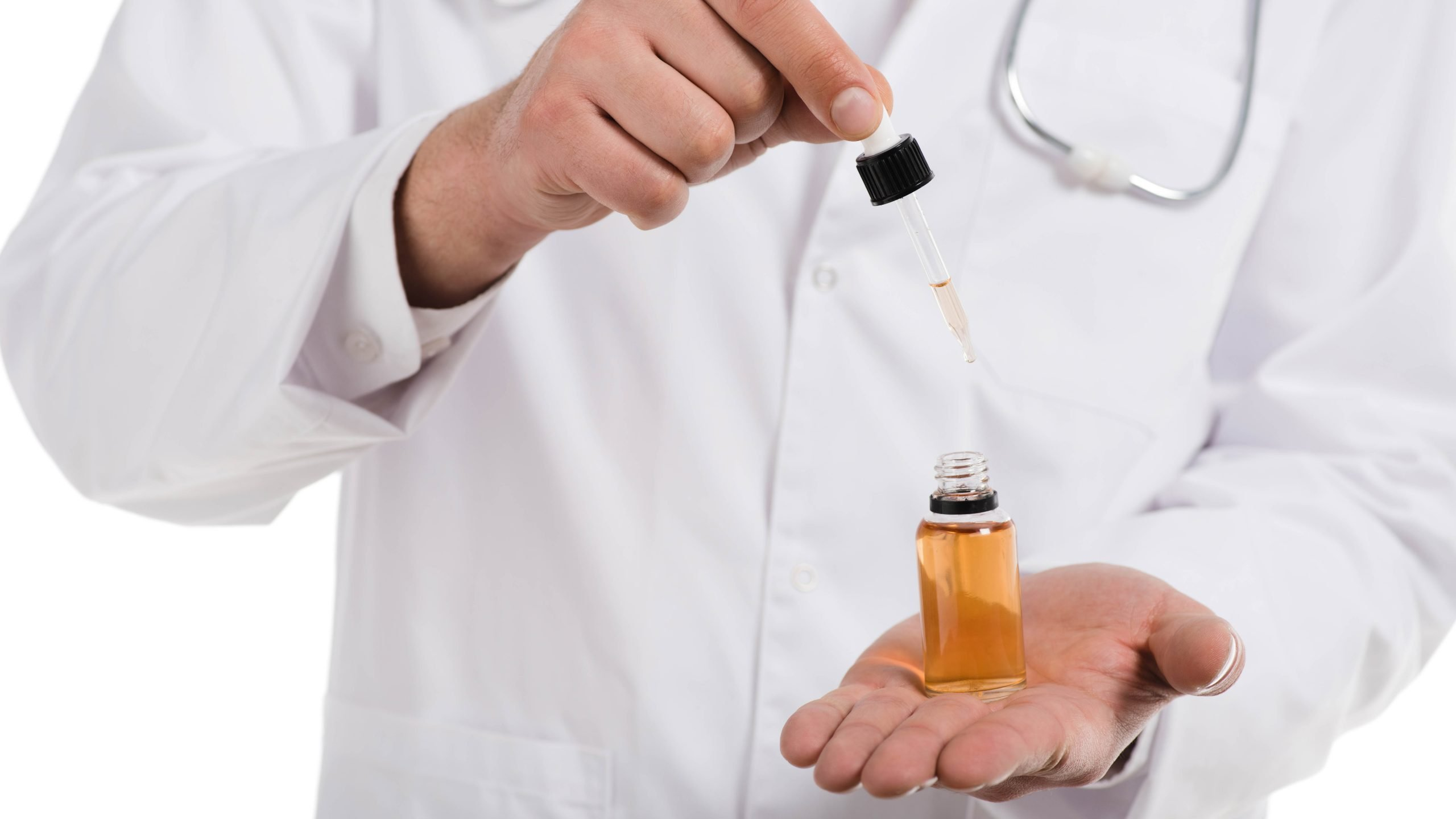 Doctor holding a cbd oil dropper and bottle in his hand in white background