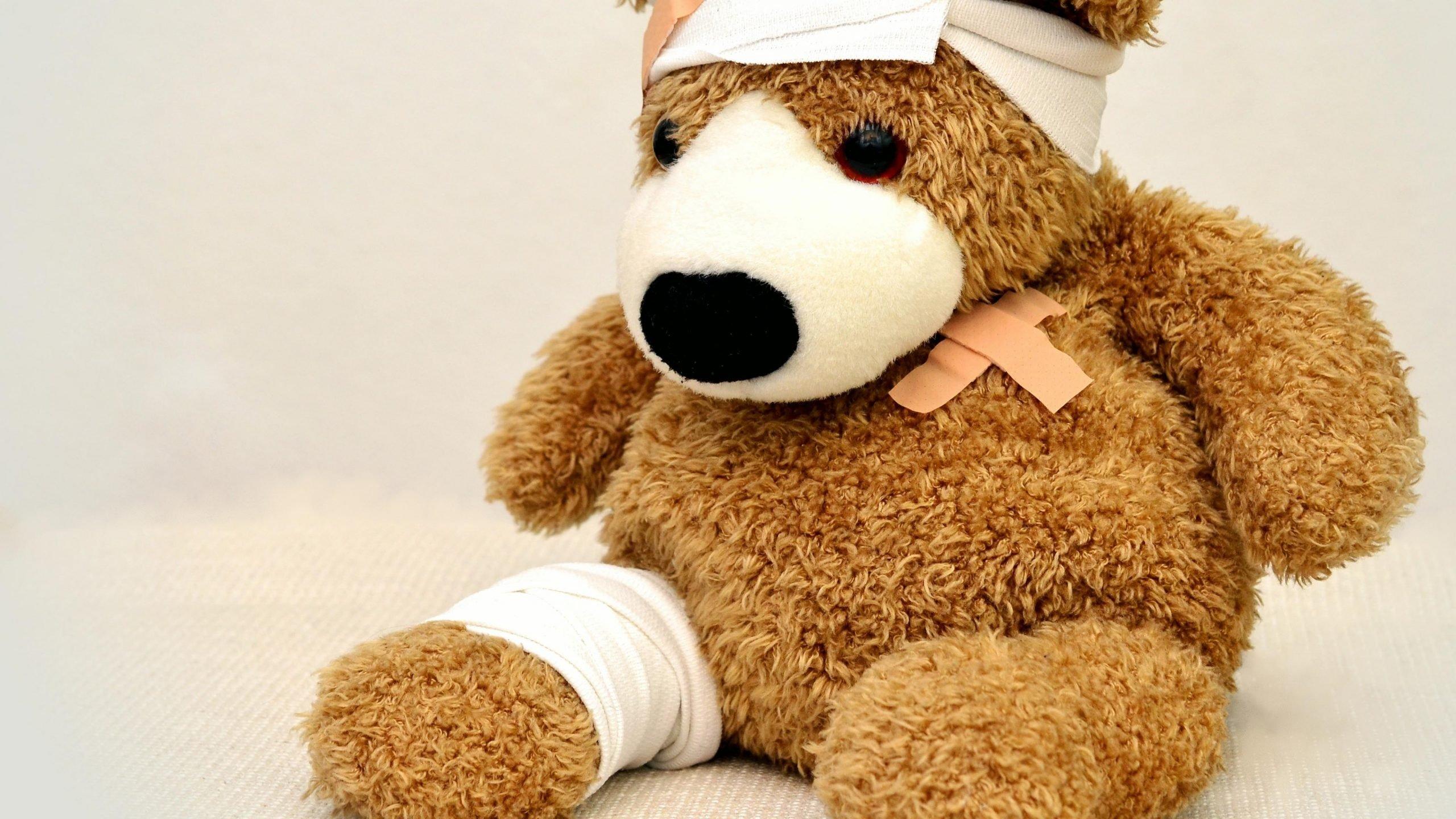 teddy bear full of bandage sitting in a corner room