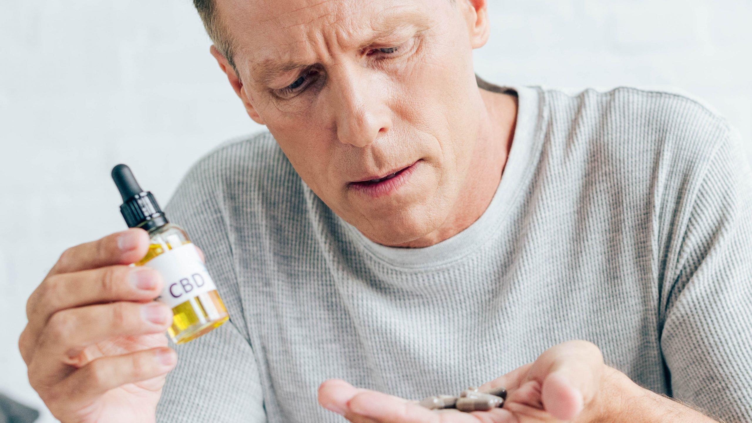 man in grey shirt using cbd oil for pain