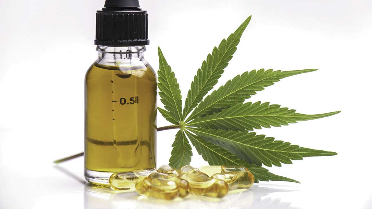 CBD oil and capsules next to hemp leaf in a white background