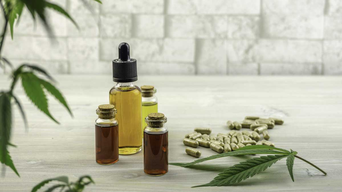 CBD products including soft gel standing together with hemp leaves