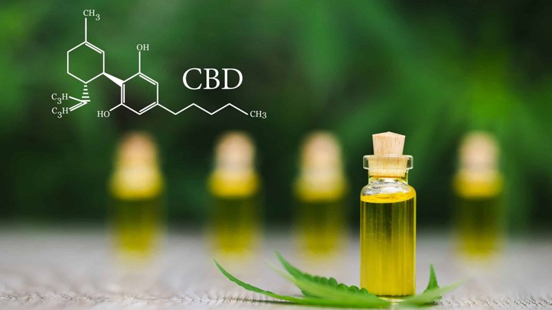 Close up image of a CBD oil in front of four other CBD oil bottles in the background with cannabidiol chemistry structure