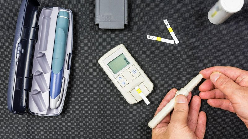a person is testing blood sugar level for diabetes type 2