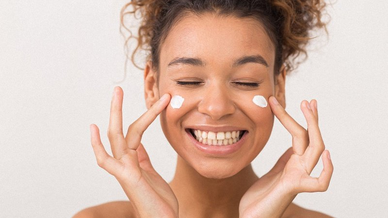 Woman happily applying skincare cream on her face