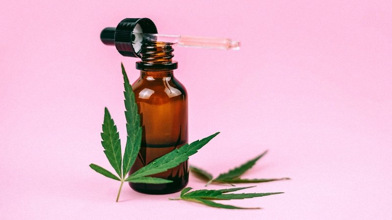 CBD Oil with Hemp Leaves in Pink Background